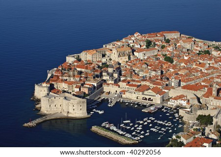 Aerial view of the walled city of Dubrovnik surrounded by the calm waters of the Adriatic Sea on the southern tip of Croatia. - stock photo