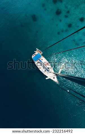 Aerial view of the yacht anchored in calm sea with couple lying on the deck - stock photo