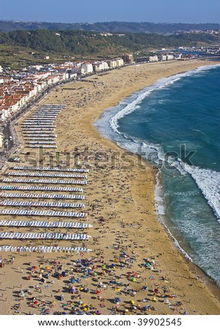 Aerial view of tourists on a busy beach by the ocean