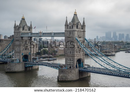 Aerial view of Tower Bridge and the skyscrapers of the financial district of Canary Wharf surrounded by low clouds on an overcast and foggy day  - stock photo