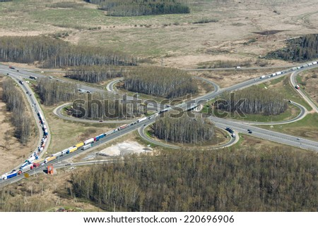 Aerial view of traffic jam at the exit of a classic cloverleaf transport intersection - stock photo