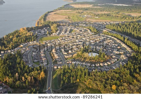 Aerial view of tree and home covered hilltop - stock photo