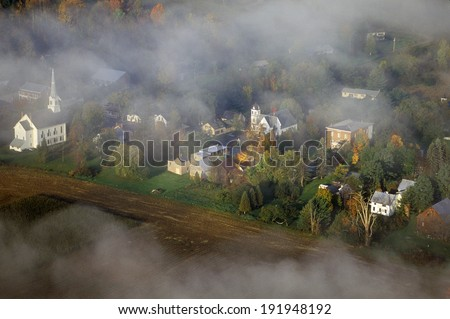 Aerial view of Waitsfield, VT in fog with church steeple on Scenic Route 100 in Autumn - stock photo