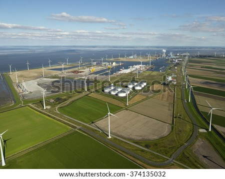 Aerial view of wind turbine farm and the petrol industrial zone from the Vopak terminal in the Eemshaven, The Netherlands.  - stock photo