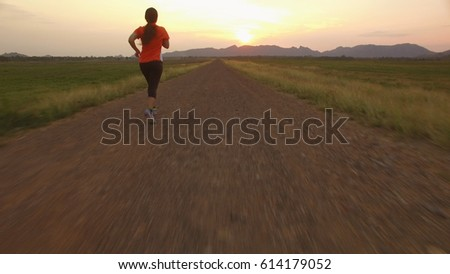 Aerial view of woman running on a rural road during sunset in the mountains