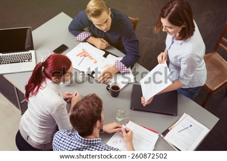 Aerial View of Young Business Friends Discussing the Project at the Worktable. - stock photo