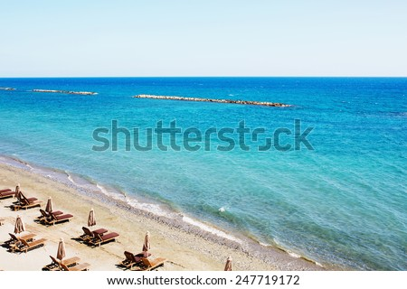 Aerial view on a beach chairs and umbrellas on sand beach. Turquoise sea water. Concept for rest, relaxation, holidays, spa, resort.  - stock photo