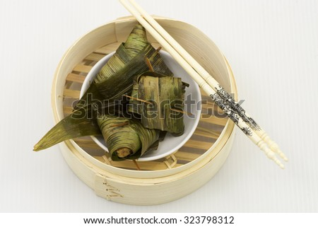 Aerial view on minced meats mixture wrap with pandan leaf. A dim sum style Chinese cuisine prepared as small bite-size portion of food traditionally served in small plate in bamboo steamer basket. - stock photo