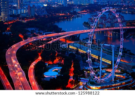 Aerial view on Singapore Flyer from roof Marina Bay Sands at night - stock photo