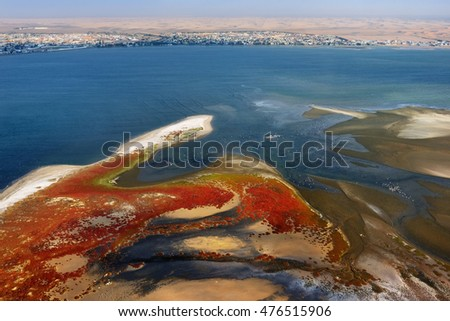 Aerial view on the sandbank in the Atlantic ocean near a coast in Namibia and the city Walvis Bay on background, Africa