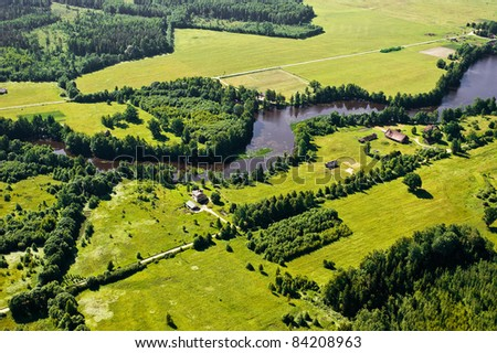 aerial view over river and rural fields - stock photo