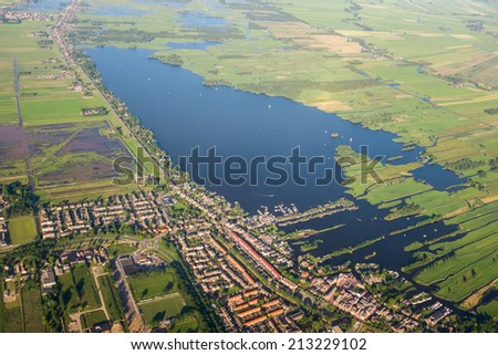 Aerial view over the Amsterdam suburbs with canals, houses fields and lake. Holland - stock photo