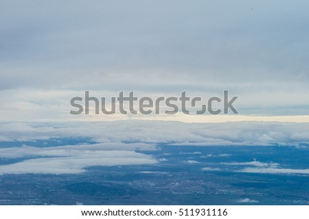 aerial view over the clouds on blue sky. blue sky and clouds and fields visible through them from a plane window