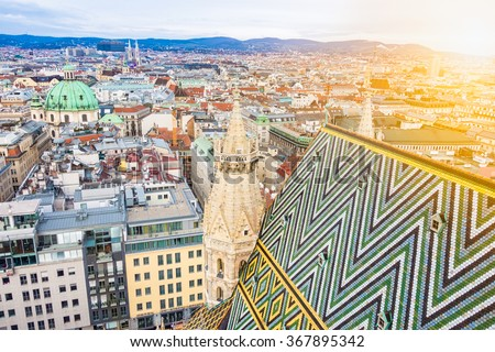 Aerial view over the rooftops of Vienna from the south tower of St. Stephen's Cathedral including the cathedral's famous ornately patterned, multi colored roof created by 230,000 glazed tiles, Austria - stock photo