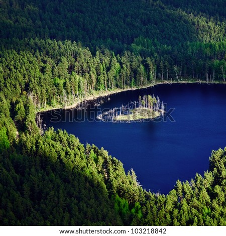 aerial view over the small lake and island surrounded by forests - stock photo