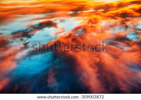 Aerial view to colorful orange and blue dramatic sky with clouds for abstract background - stock photo