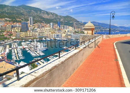 Aerial view to the main harbor and distant buildings of Monte Carlo seen from the medieval walls of Monaco-ville, Monaco - stock photo