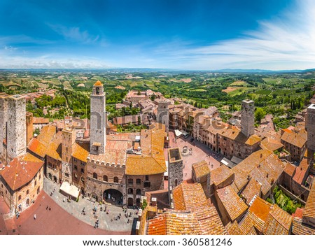 Aerial wide-angle view of the historic town of San Gimignano with tuscan countryside on a sunny day, Tuscany, Italy - stock photo