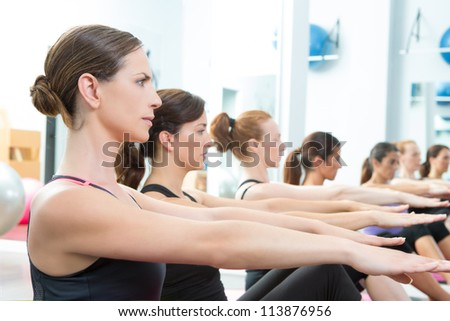 Aerobic Pilates personal trainer in a gym group class in a row - stock photo