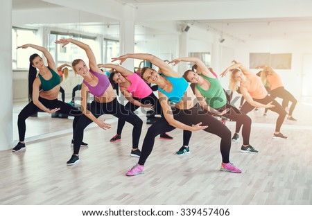 Aerobics class at a gym with a group of attractive fit young women in colorful sportswear working out in together, in a wellness, health and fitness concept - stock photo