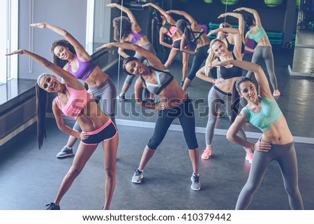 Aerobics with girls. Young beautiful cheerful women with perfect bodies in sportswear exercising and looking at camera with smile at gym - stock photo