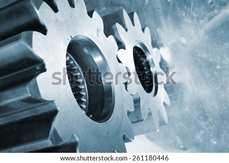 aerospace titanium gears and cogwheels against aluminum background, blue toning. - stock photo