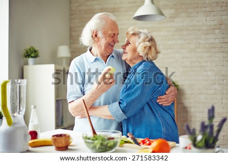 Affectionate and happy seniors embracing by kitchen table - stock photo