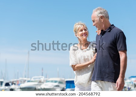 Affectionate attractive mature couple at the sea standing smiling into each others eyes in front of a marine harbour - stock photo
