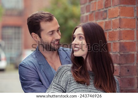 Affectionate attractive young couple standing alongside a brick wall in an urban street smiling into each others eyes - stock photo