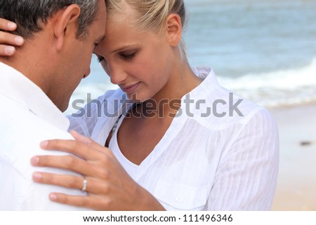 Affectionate couple dressed in white at the seaside - stock photo
