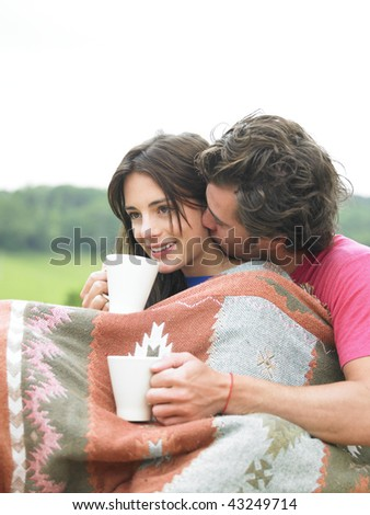 Affectionate couple drinking tea outdoors. Vertical. - stock photo