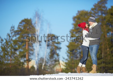 Affectionate couple in knitted winterwear spending leisure outdoors - stock photo