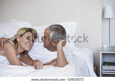Affectionate couple looking in each others eyes, lying in bed - stock photo