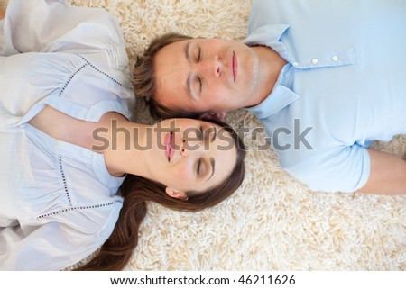 Affectionate couple lying on the floor with heads together