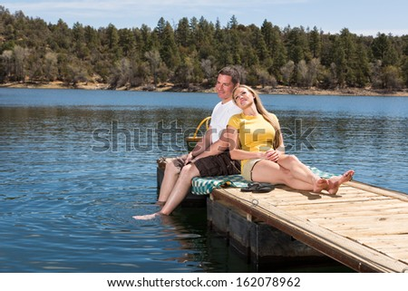 Affectionate Couple on Lakeside Dock - stock photo