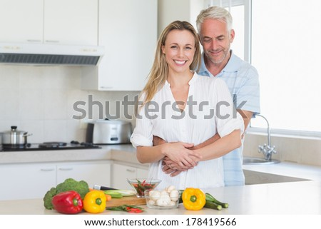 Affectionate couple preparing a healthy dinner together at home in the kitchen - stock photo