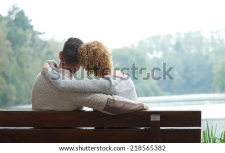 Affectionate couple sitting together on bench by the lake  - stock photo