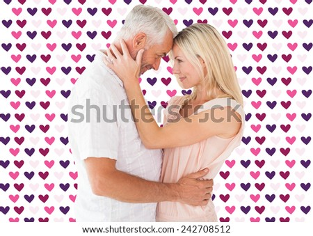Affectionate couple standing and hugging against valentines day pattern - stock photo