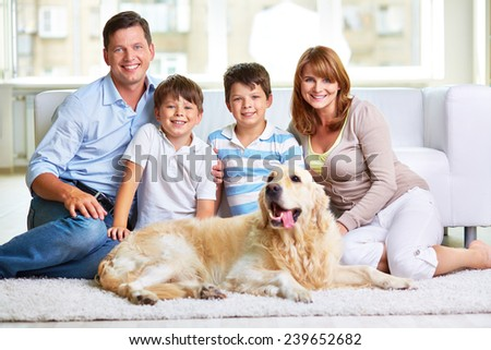 Affectionate couple, their kids and pet spending weekend at home - stock photo