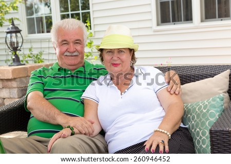 Affectionate elderly couple relaxing on an outdoor patio sitting arm in arm on a garden sofa in front of their house smiling at the camera - stock photo