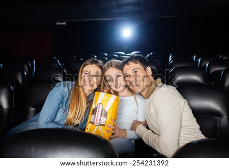 Affectionate family of three watching film in movie theater - stock photo