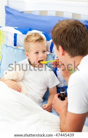 Affectionate father giving cough syrup to his sick son sitting on bed - stock photo