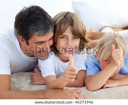 Affectionate father with his children having fun lying on a bed