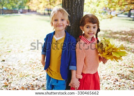 Affectionate friends standing by tree trunk and looking at camera