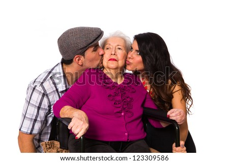 Affectionate grandchildren with their elderly handicapped grandmother on a white background.