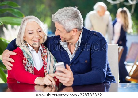 Affectionate grandson and grandmother using smartphone with family in background at nursing home - stock photo