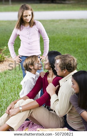 Affectionate interracial family of five enjoying picnic together in park - stock photo