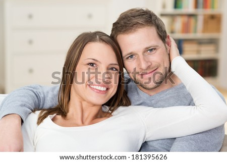 Affectionate loving young couple relaxing at home sitting together on a sofa arm in arm smiling at the camera - stock photo