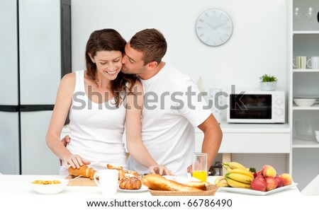Affectionate man kissing his girlfriend while cutting bread for breakfast in the kitchen - stock photo
