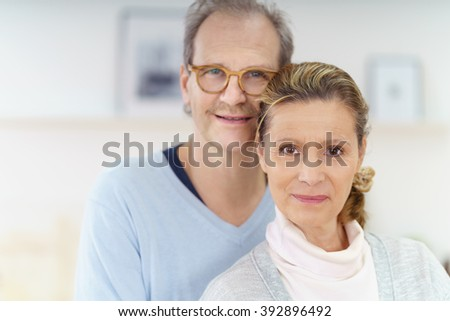 Affectionate middle-aged couple smiling at camera - stock photo